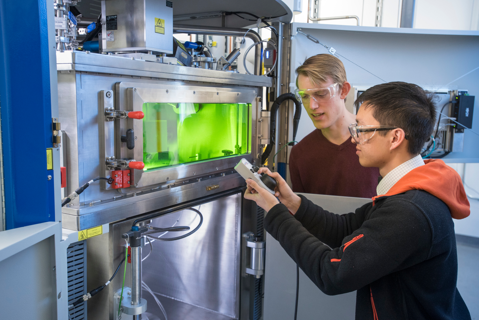 (front) Cain Hung, Graduate Student in Material Science and Engineering and Andrew Budd '16 (ENG) using an IPG Open-Architecture Metal Powder Bed Fusion System at the Innovation Partnership Building (IPB) on Dec. 5, 2018. (Al Ferreira/UConn Photo)